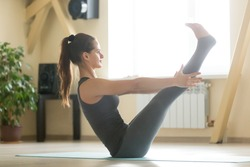 Young attractive happy woman practicing yoga, stretching in Paripurna Navasana exercise, boat pose, working out, wearing grey sportswear, indoor full length, home or sport club interior background