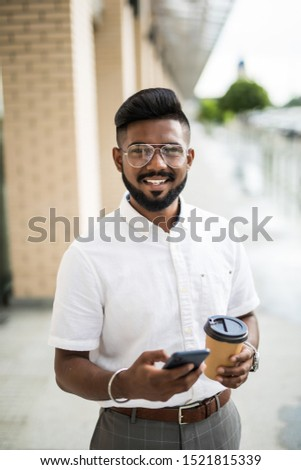 Young attractive hipster guy dressed in trendy outfit monitoring information from social networks via cellphone connecting to 4G internet while enjoying coffee to go strolling on megalopolis street #1521815339