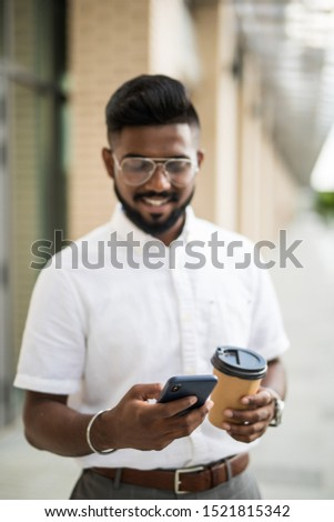 Young attractive hipster guy dressed in trendy outfit monitoring information from social networks via cellphone connecting to 4G internet while enjoying coffee to go strolling on megalopolis street #1521815342