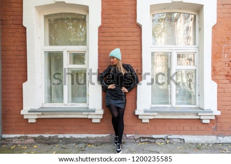 Young attractive lady in blue knitting hat and black coat posing. Smiling beautiful hipster happy woman in city street, wearing stylish clothes. Autumn trend, urban stydent style.