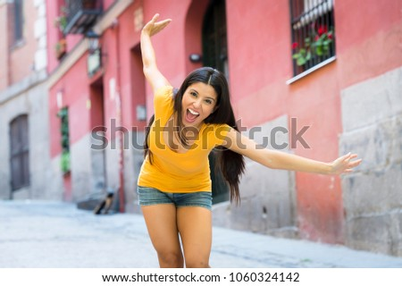 young attractive latin woman happy and excited posing on modern urban European city background in tourism and holiday travel concept