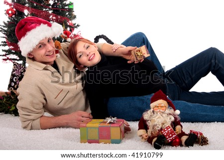 Young attractive loving couple, man and woman  in Christmas setting at home. Studio, white background.