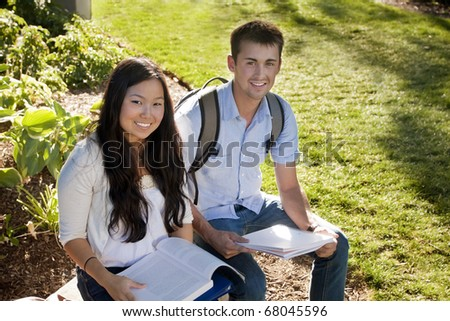 Young, attractive male and female students outside studying