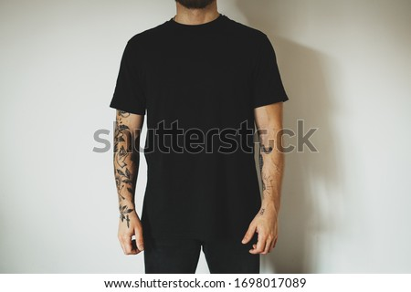 young attractive male hipster with a beard and tattoos, dressed in a black blank t-shirt, posing on a white wall background. Empty space for you logo or design. Stock fotó ©