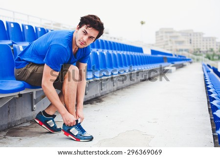 Young attractive male model in blue shirt  tying laces on his running shoes and looking at field before run on a stadium stands after workout perspective view. Copy space