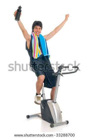 Young attractive male teenager on fitness bike, bicycle. Studio shot, white background.