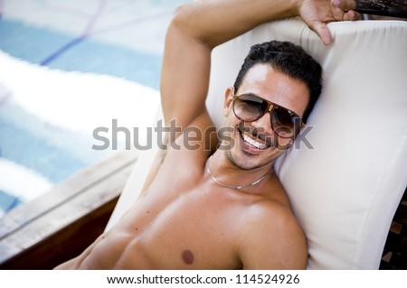 Young attractive man at the swimming pool