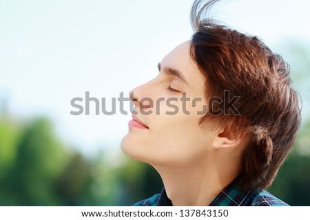 Young attractive man breathing fresh air outdoors showing his face to the wind