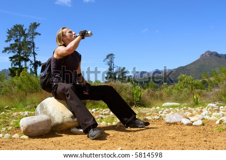 Young attractive man drinks water - misty majestic mountains as a background. Shot in Jan Marais nature reserve, Stellenbosch, Western Cape, South Africa.