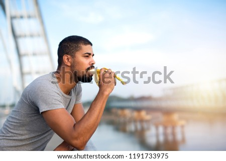 Young attractive man eating banana fruit on the bridge overlooking the river. Healthy lifestyle and nourishment.  #1191733975