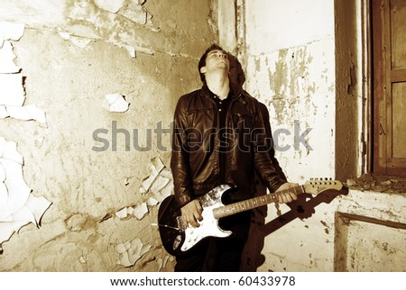 Young attractive man guitar player and singer inside empty room with old vintage wall