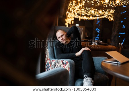 Young attractive man in a black stylish shirt in stylish jeans in sneakers sits in a beautiful restaurant and works at the computer waiting for lunch. Handsome modern guy on vacation.