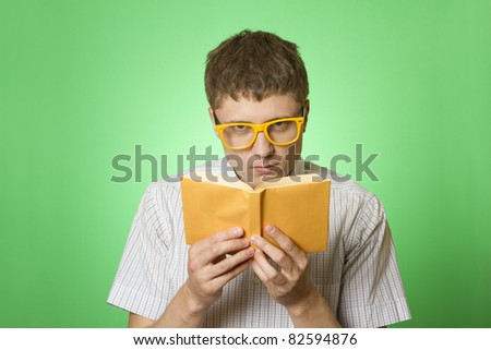 Young attractive man in a shirt and yellow glasses, bow tie on a green background reads the yellow book. Bookworm