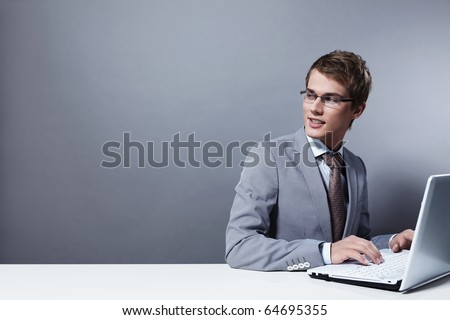 Young attractive man in a suit with the laptop looks back
