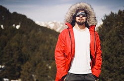 Young attractive man in a sunglasses, red jacket and a white t-shirt standing on a top of snow mountain on a sunny day. Horizontal mock-up.