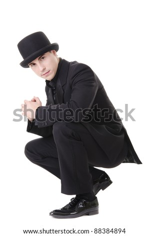 Young attractive man in black suit and hat isolated on white background