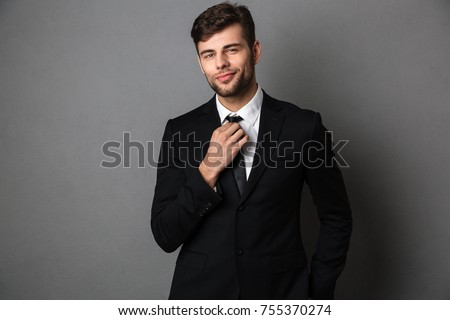 Young attractive man in classic suit straightens his tie, looking at camera, isolated on gray background