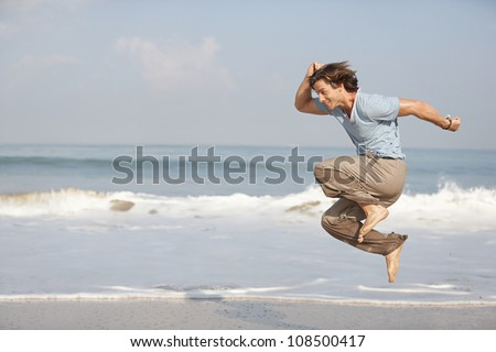 Young attractive man jumping by the sea shore while on vacation.