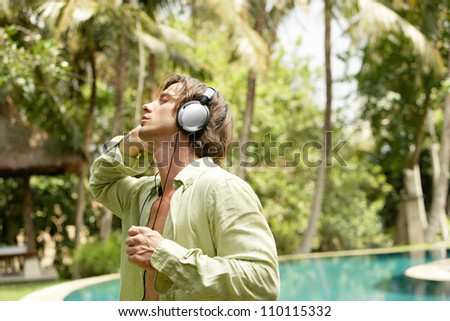 Young attractive man listening to music with headphones while dancing near a swimming pool in a tropical garden.