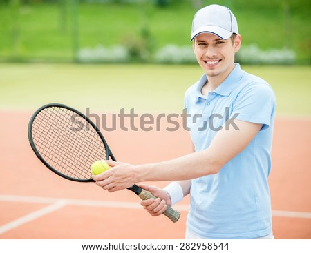 Young attractive man play tennis at court in the morning