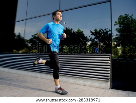 young attractive man running and training on urban street background on summer workout in sport practice and healthy lifestyle concept