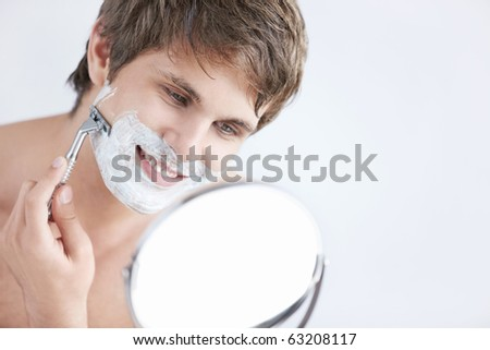 Young attractive man shaves in the mirror