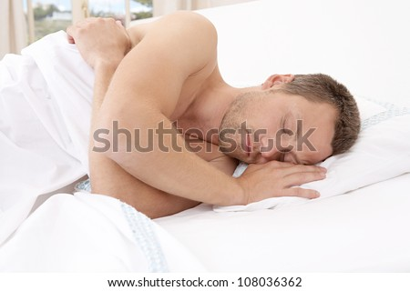 Young attractive man sleeping in bed.