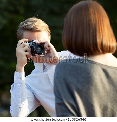 young attractive man taking photos of his girlfriend in the park