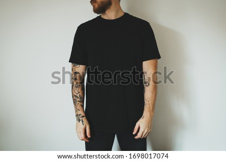 young attractive man with a beard and tattoos, dressed in a black blank t-shirt, posing against a white wall. Empty space for you logo or design. Stock fotó ©