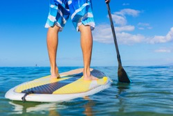 Young Attractive Mann on Stand Up Paddle Board, SUP, in the Blue Waters off Hawaii