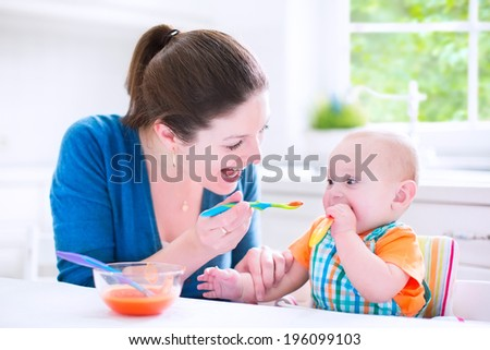 Young attractive mother feeding her cute baby son giving him his first ...