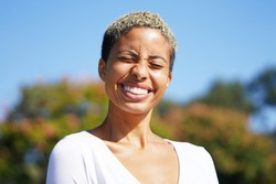 Young attractive multicultural woman outside in Balboa Park against the sky and trees with short hair and a v neck white shirt in the sun, wincing and smiling with eyes closed