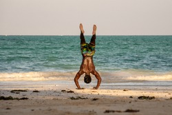 Young Attractive Muscular and Strong Athletic Black African Man at the White Sand Beach Training Acrobatics and Handstand