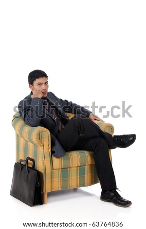 Young attractive nepalese businessman sitting on armchair, waiting. Briefcase beside. Studio shot, white background.