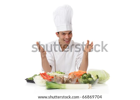 Young attractive nepalese man chef presenting variety of fresh vegetables. Ingredients for oriental food. Studio shot, white background.