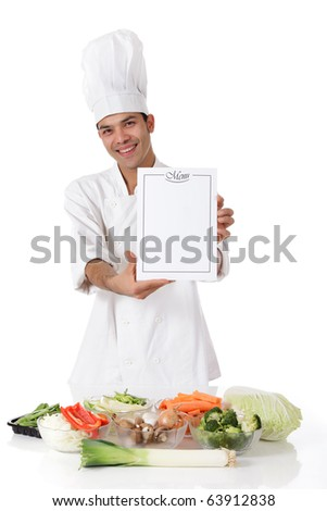Young attractive nepalese man chef showing the menu list, blank page. Variety of fresh vegetables on table. Studio shot, white background