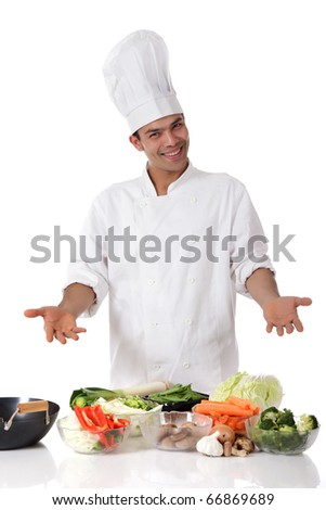 Young attractive nepalese man chef showing variety of fresh vegetables. Ingredients for oriental food. Studio shot, white background.