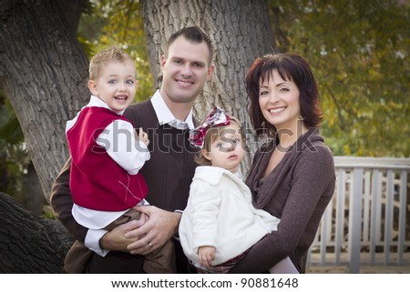 Young Attractive Parents and Children Portrait Outside in the Park.