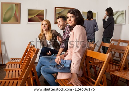 young attractive people sitting down on wooden chairs at an abstract photography exhibition, enjoying themselves, with other people looking at art works on background