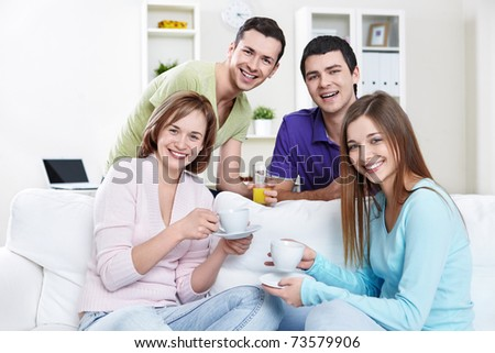 Young attractive people with drinks at home