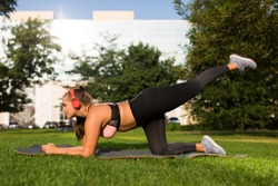 Young attractive plus size woman in sporty top and leggings with red headphones doing sport exercises on yoga mat in city park