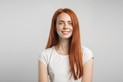 Young attractive redhead girl smiling looking at camera.