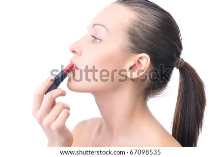 young attractive sensual woman is applying cosmetics on her face, side view, isolated on white