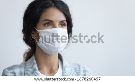 Young attractive serious woman in protective facial medical mask posing over blue background with copy space for text. Coronavirus COVID19 pandemic infection outbreak prevention, personal care concept