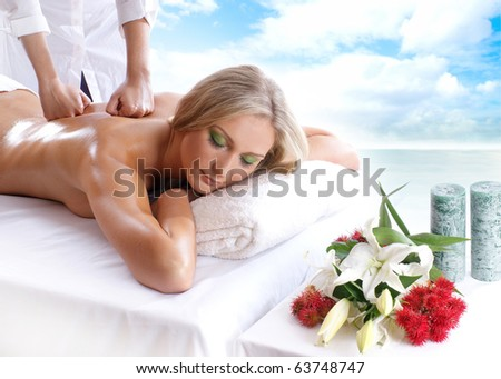 Young attractive sexy blond getting massage treatment isolated over white background