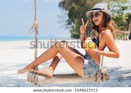 Stock Photo young attractive sexy woman on vacation sitting on swing by sea, tropical beach, drinking cocktail in coconut, skinny legs, traveling in Thailand, smiling, happy, positive emotion, summer style