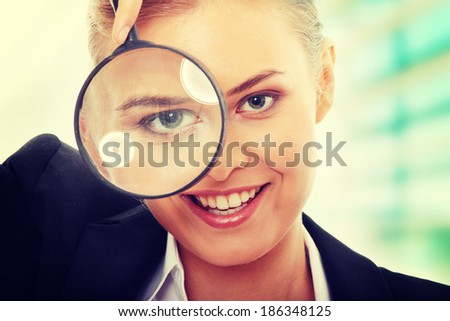 Young attractive smiling business woman looking into a magnifying glass