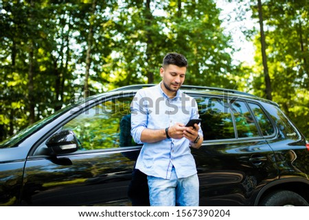 Young attractive smiling man with beard standing near his car and holding mobile phone Foto stock ©