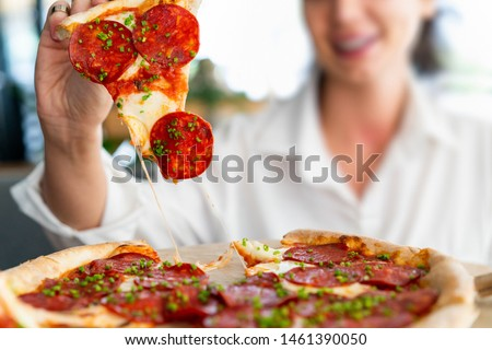 Young attractive smiling woman eating pizza at street cafe. Cheat meal. Cheat day