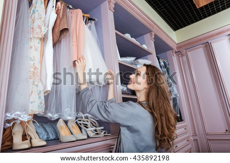 Young attractive smiling woman searching what to wear in a wardrobe